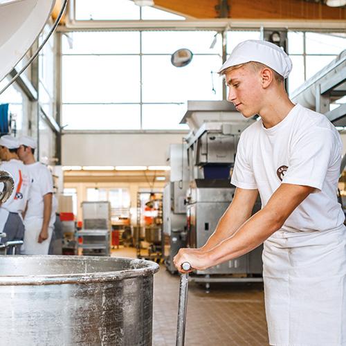 Bäcker-Azubi beim Teigmachen in der Backstube
